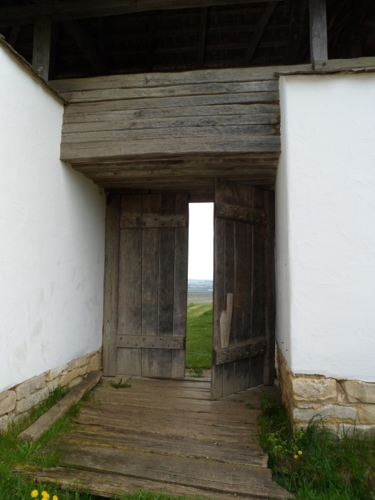 A double wooden gate in a plastered wall on a stone foundation