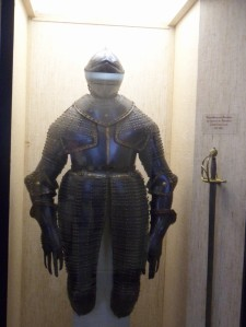 Suit of black plate armour with a closed helmet, articulated pauldrons, and tassets which flare at the hips and extend below the knees