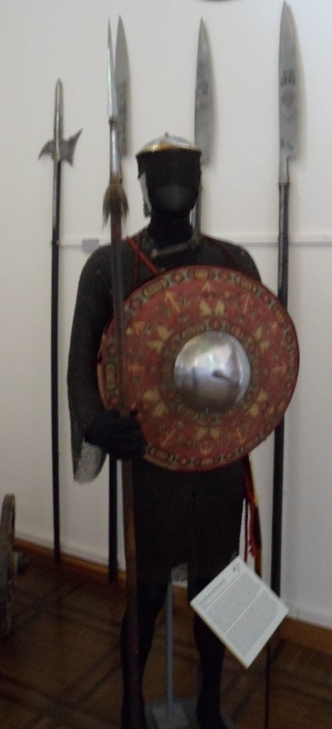 An armour on a stand consisting of a long-sleeved shirt of mail, a shallow round steel helmet with a skirt of mail suspended from it, a domed wicker shield with a steel boss, and a broad-bladed spear