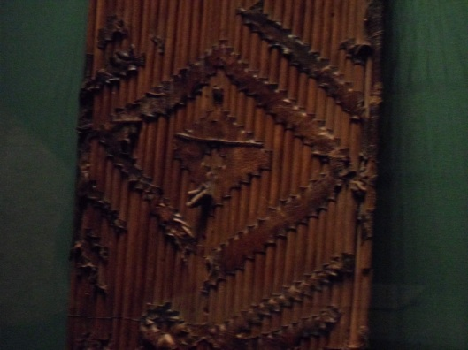 Closeup photo of a shield of sticks thrust through zigzag slits in a sheet of leather