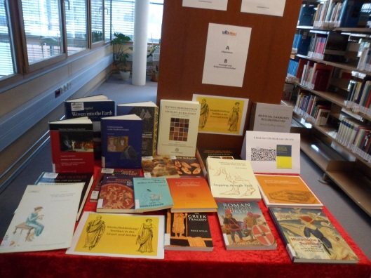 Table in a library with a variety of books on ancient clothing spread across it cover-up
