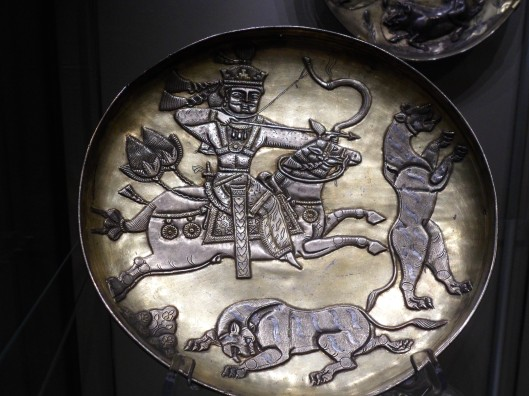 Wrought and gilt silver plate with relief of a crowned archer on horseback shooting panthers