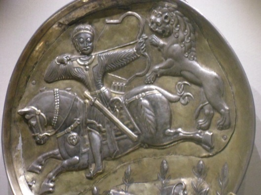 Wrought silver bowl with relief of bare-headed archer on horseback shooting a lion which pounces on his horse from behind.