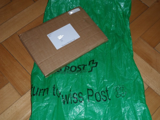 A folding slip of corrugated cardboard with a printed label carrying the address, over a green nylon bag a metre long and 50 cm wide labeled Swiss Post
