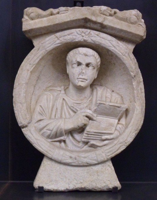 A stone relief of a bare-headed beardless man holding six writing boards and a stylus