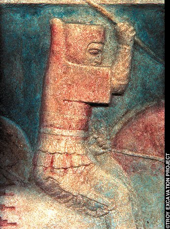 A painted relief of a warrior on horseback stabbing downwards with a spear. His body armour has two layers of short flaps at the waist, a front and back running straight up and down, wide blocky sleeves ending before the arm joint, and a tab behind the head just as tall as the head.