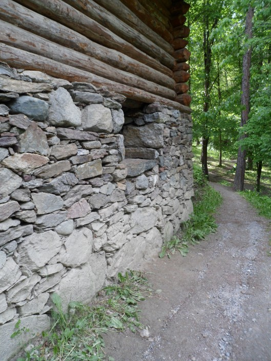 A path running through light woods with a building at the side with a lower story built from fieldstone and an upper story built from logs with their ends crisscrossed at the corners