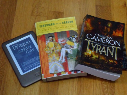 "Three books sitting on a hardwood floor: ""The Dragon of the Ishtar Gate"" on an eReader, ""Flashman and the Dragon"" in paperback, and ""Tyrant"" in paperback"