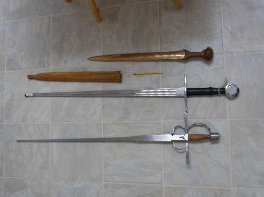 Three swords and a solid wood scabbard on a textured linoleum floor with a pencil for scale