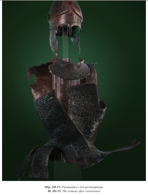 A photo of an armour comprising a Chalcidian helmet with hinged cheeks, a leather gorget covered in iron scales, and a leather cuirass with a skirt of feathers and two shoulder-flaps (aka. Jarva type IV/tube-and-yoke/linothorax) completely covered with iron scales