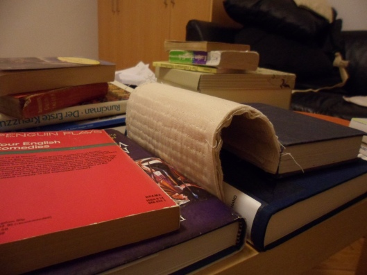 Photo of the test patch supported vertically between the spines of two hardcover books and bent through half a circle with the opposite edge resting against the spine of a third hardcover book