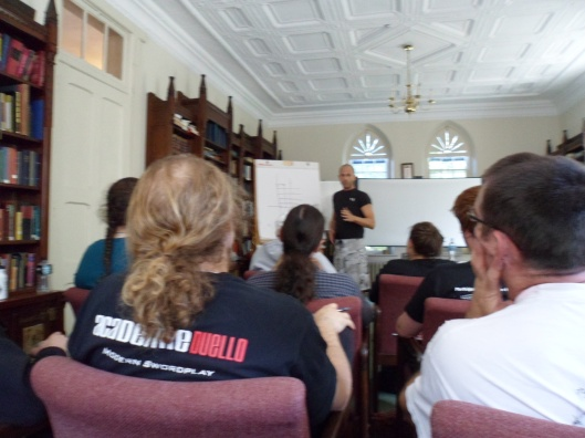 A library in a Neo-Gothic building with an athletic-looking man in shorts and a teeshirt talking in front of a portable whiteboard while an audience in chairs listens.