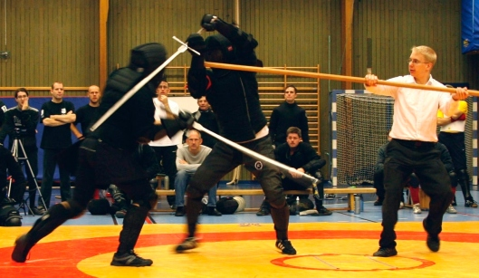 Two fencers in black clothig, gym shoes, and black fencing masks fight with longswords. A group of fencers in black sits on benches and watches