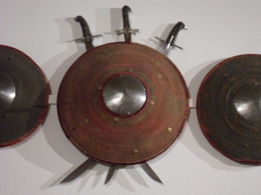 A round, domed wicker shield with a spiked steel boss and a cloth-bound rim.  Three short scimilars hang behind it with their handles up and blades crossed at the middle.