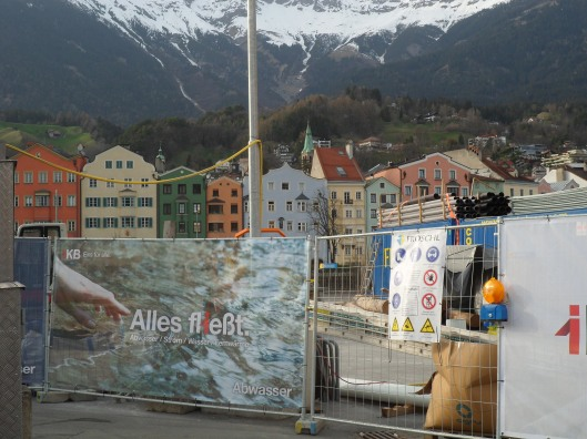 """A steel construction fence of wires and tubes with tall stone houses and snowy mountains in the background.  A panel of cloth on the fence has a photo of a hand reaching towards a stream and the label """"Alles fließt"""""""
