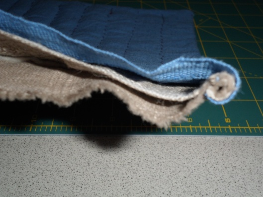 View of layers from the unfinished selvedge: blue linen-cotton blend above loosely-woven unbleached linen above 100% cotton quilt batting above densely-woven unbleached linen.  Side seams are rolled over then whip-stitched to the densely-woven unbleached linen