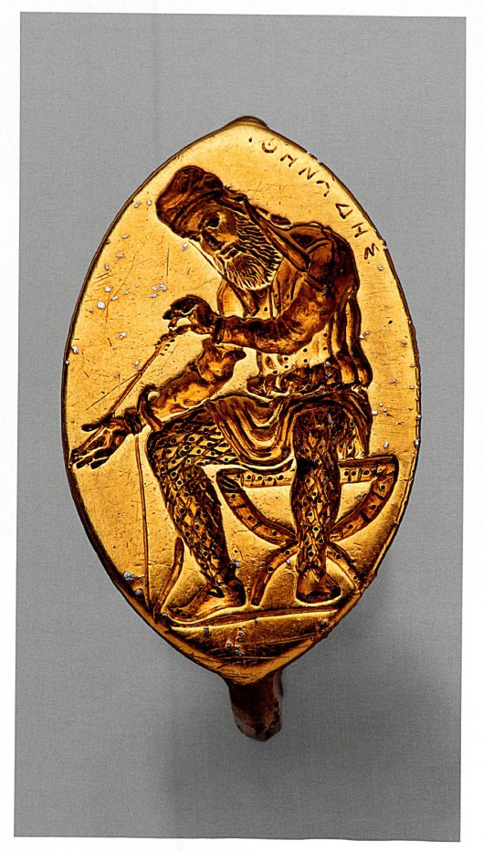 The oblong face of a signet ring depicting a man in tunic and trousers and hood sitting on a folding chair with a bow at his knee and examining an arrow.