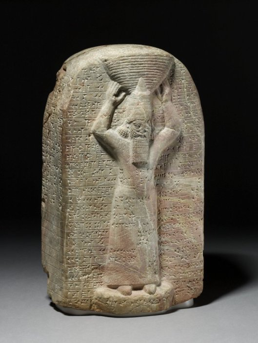 A blocky marble stelae with a cunform inscription and a man with a tall hat carrying a basket on his head.