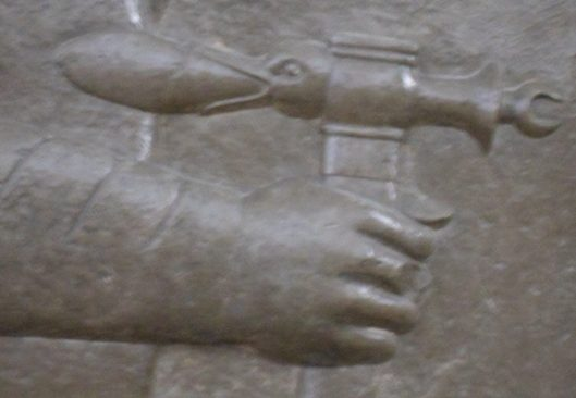 A relief of an axe carved into smooth, dark stone