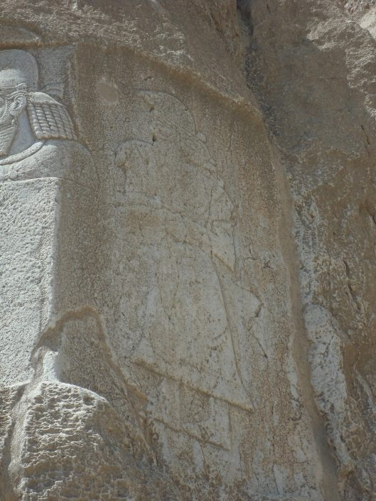 A shallow relief sculpture of a man with a long robe wrapped around his body