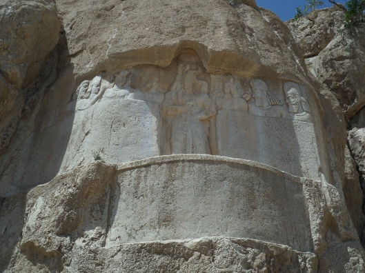 A relief set deep into a mountainside of seven men standing on either side of a tall, crowned figure holding a sword