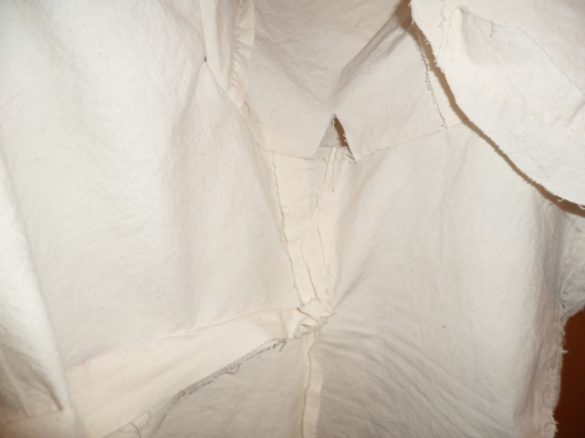 The inside of a white cotton jacket with many visible modifications and unfinished seams