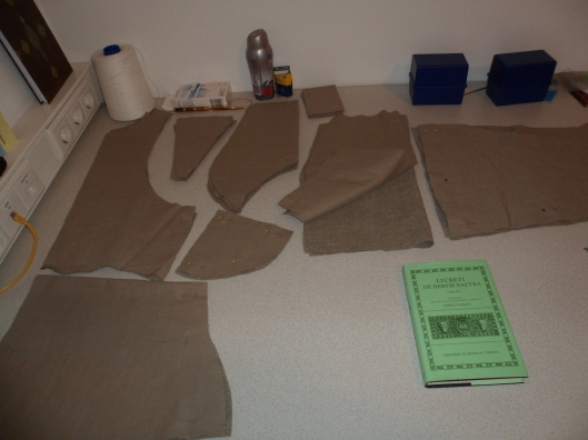 Piles of cut cloth for a jacket on a tabletop, with two types of cloth per pile