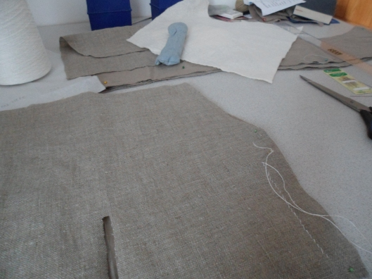 Two layers of the upper sleeve laid upon a table, coarse linen up, with a line of coarse white thread near one edge