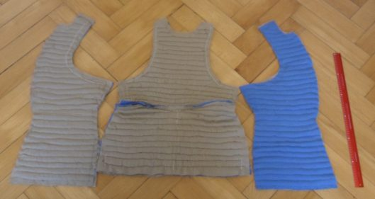 Components of a quilted doublet spread on the floor showing that one breast has blue cloth on the inside and one has brown there