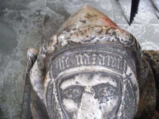 A smooth stone effigy of a knight wearing a pointed bascinet with aventail
