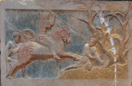 In another part of the Achaemenid empire, a cavalryman in hood and body armour rides down his enemies with a spear.  Cropped from a photo y Dan Diffendale https://www.flickr.com/photos/dandiffendale/10506953106 under a Creative Commons CC BY-NC-SA 2.0 license.