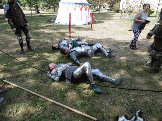 Several men and women in plate armour rest on the grass in the shade while others look on or chat