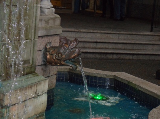 A stone fountain with copper spouts in the forms of fish-heads