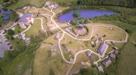 A living history village with fields and a lake from the air