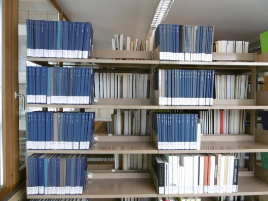 A steel bookcase full of hardcovers bound in blue cloth