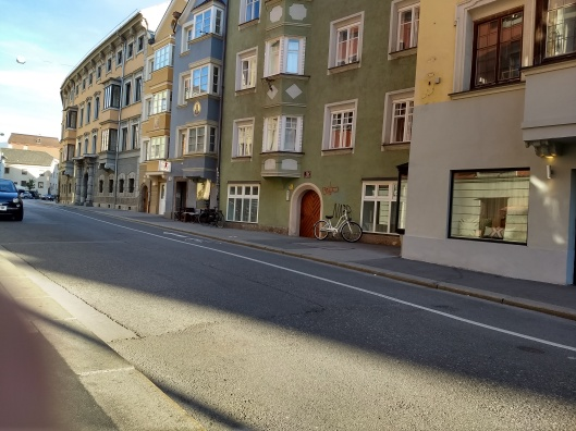 A street which slopes visibly upwards, so that there are steps down from the sidewalk to the ground floor of the shops