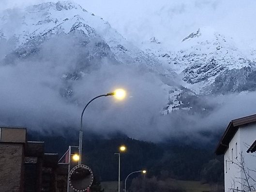 A snowz foggy mountain range with green woods below and streetlights turning on
