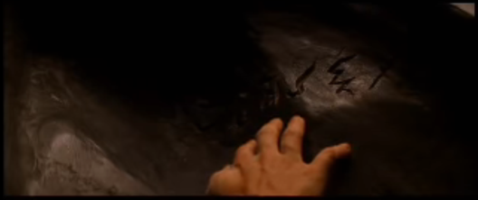 """A pale-skinned hand examines an inscription scratched into black stone, from Stephen Sommers' film """"The Mummy"""" (1999)"""