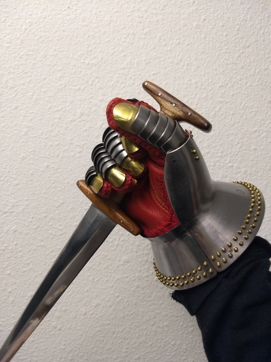 A gauntleted hand gripping a dagger.  There is significantly less space between the top of the hand and the pommel bar