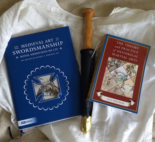 Two books with a wooden rondel dagger in a leather scabbard with a brass chape between them, laying on top of a hand-sewn linen shirt