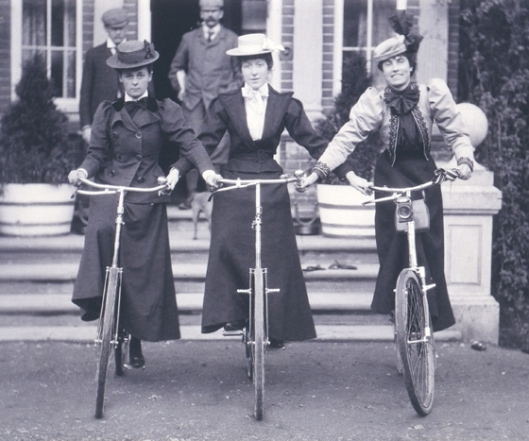 Three women in dressnding on bicycles with straight handlebars