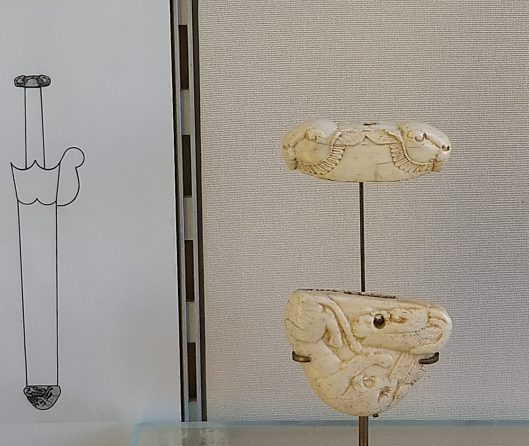 a carved ivory pommel with ruminant heads and a scabbard chape with a great cat pouncing on a ruminant