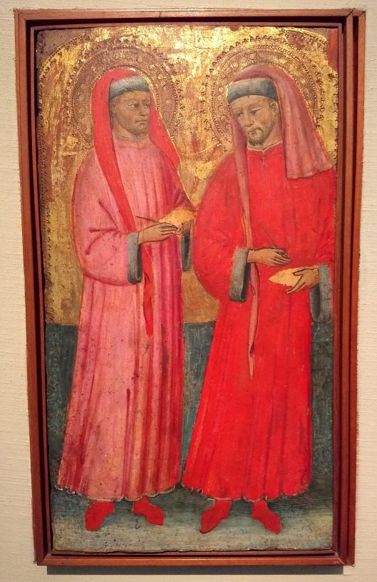a painting on wood of two medievla scholars with waxed tablets in their hands wearing long red and pink robes with furred cuffs and chaperone-hats with long tails hanging at their right breast and the skirt of their hood hanging at the left breast