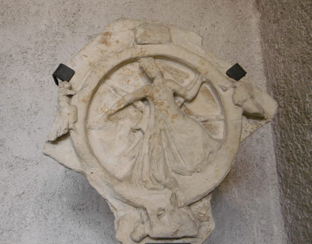 a broken carving of Lady Fortune turning her wheel,with four figures being carried up, standing proud atop, desperately trying not to slide off, and hanging from the bottom
