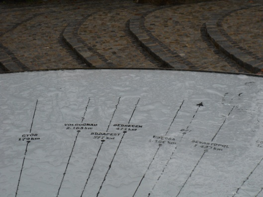 "A round table on a stone patio with lines pointing to Györ 179 km, Volgograd 2165 km, Budapest 277 km, Debrecen 471 km, ""east,"" and Sevastopol 1427 km"