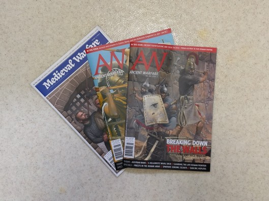 three issues of Ancient Warfare and Medieval Warfare magazine spread out on a textured linoleum surface